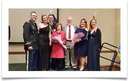 On Stage L-R: LTC Joshua Mau, His Wife Kelly, Matthew Walters, Raqui, Col. Ed Ramsey Jr., Kristin Walters, Cadet Ashley