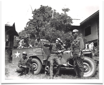 Maj. Claro Camacho, Chief signal officer of ECLGA with Radio Operators Cordero and Acosta and driver, Delfin Domingo with Jeep captured from the Japanese